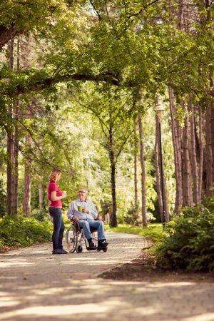 Foto de Mujer sonriente con su padre feliz discapacitado en tiempo de disfrutar de silla de ruedas en el Parque - Imagen libre de derechos
