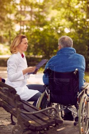Checking up the history of the patient in wheelchair