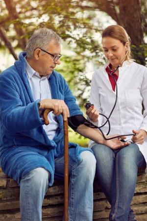 Photo pour Hôpitaux, laboratoires et cliniques Évaluation infirmière de la pression artérielle chez l'homme âgé - image libre de droit