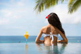 Back view of young woman in bikini drinking cocktail