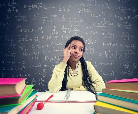 Photo pour Étudiante africaine pensant à de belles choses tout en étant assise sur le bureau de l'école - image libre de droit