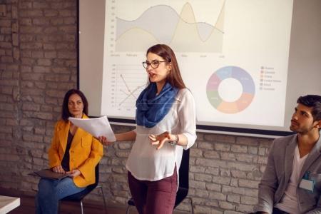 Photo pour Jeune femme tenir une réunion en entreprise - image libre de droit