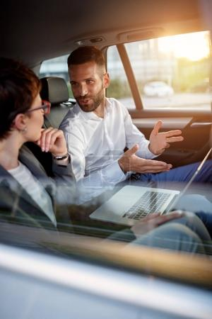 Business people working together in backseat of car