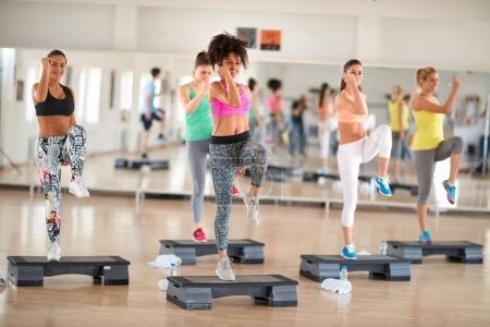 Photo for Fitness group training on stepper in colorful sportswear - Royalty Free Image