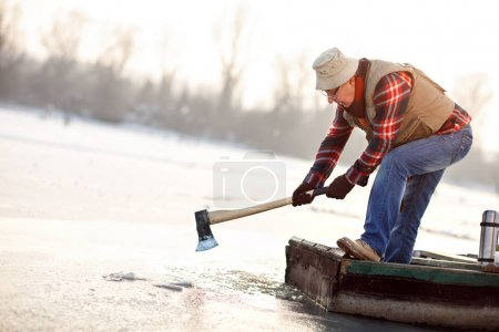 Old man in boat with axe