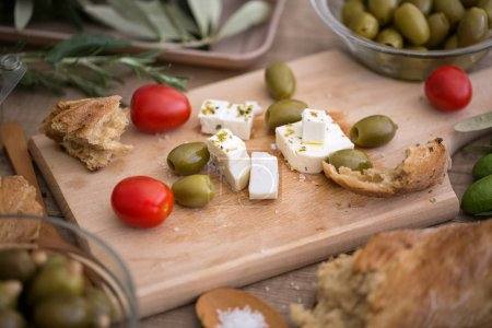 Photo for Vegetarian salad with fresh vegetables, feta cheese and green olives on wooden table - Royalty Free Image