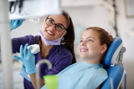 Photo pour Dentiste femme parler de nettoyage mâchoire avec peu patient - image libre de droit