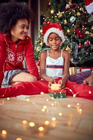 Photo pour Jolie fille ouvre un cadeau pour le matin de Noël et amusez-vous - image libre de droit