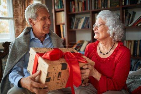 Photo pour Souriant homme et femme âgés Échanger des cadeaux de Noël - image libre de droit