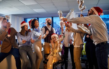 Photo for People in santa hats celebrating holiday at work.Merry Christmas - Royalty Free Image