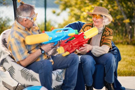 Photo for Crazy Senior man and woman.Happy senior couple on  vacation  playing with water gun. - Royalty Free Image