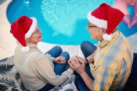 Photo for Loving smiling senior man and woman together celebrating Christmas - Royalty Free Image