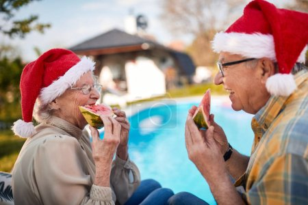 Photo for Happy senior couple in Santa hats enjoy on Christmas holiday and eating watermelon - Royalty Free Image