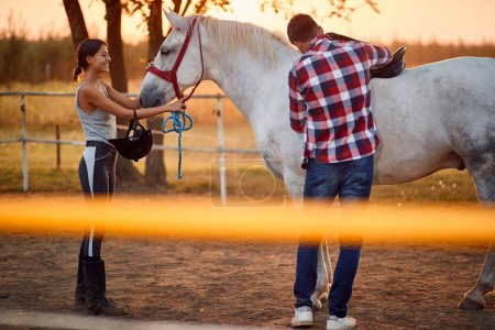 Photo for Man and a woman tending with horse riding gear, horse riding concept - Royalty Free Image