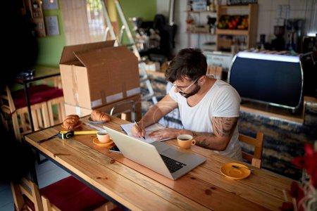 Foto de Hombre en la cafetería trabajando en el lapto.Small business owner.. - Imagen libre de derechos