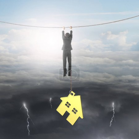 Photo pour Homme d'affaires enchaîné par la maison d'or suspendue à la corde, sur fond de ciel conditions météorologiques opposées, paysage nuageux lumineux soleil et la foudre nuageuse sombre . - image libre de droit