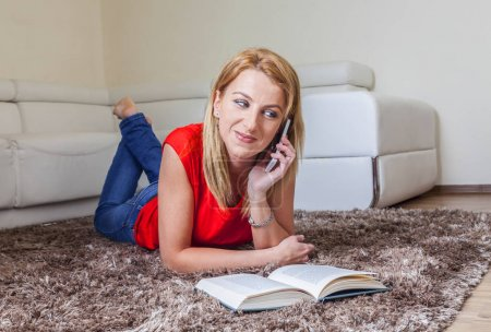 Woman talking on the Mobile phone while Reading a Book