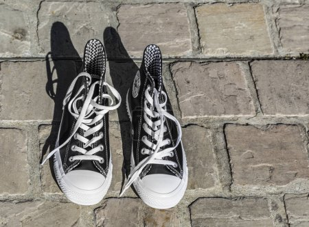 Photo pour Chartres, France - 2 septembre 2019: Image d'une paire de baskets All Star Converse dans une rue pavée. - image libre de droit