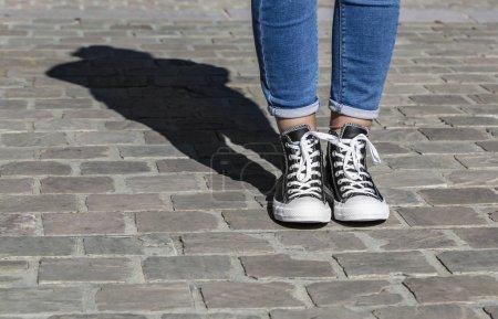 Photo pour Chartres, France - Spetember 2, 2019 : Image de la partie inférieure des jambes d'un adolescent en jeans et espadrilles All Star Converse dans une rue pavée. - image libre de droit