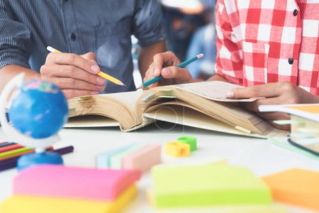 Photo for Young woman and man studying for a test or an exam. Tutor books with friends. Young students campus helps friend catching up and learning. People, learning, education and school concept - Royalty Free Image