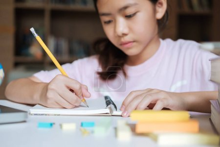 Photo for Education concept. Girl reading and writing and do homework in library of school. Seft study and learning. - Royalty Free Image