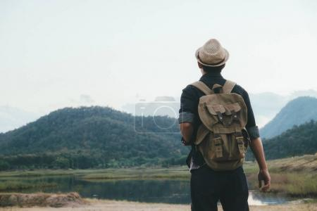 Photo pour Jeune homme voyageur avec sac à dos de détente en plein air. Vacances d'été et le concept de randonnée Lifestyle. Effet de filtre rétro, mise au point sélective - image libre de droit