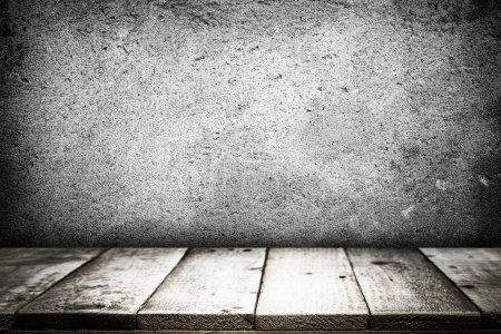 Leerer Tisch für Geschenkartikel auf grauer Betonwand.