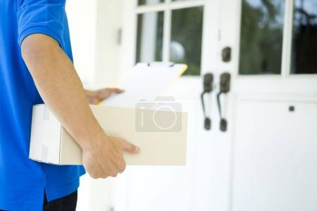 Photo for Delivery service courier standing in front of the house with boxes in hands. - Royalty Free Image