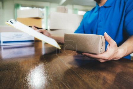 Photo for Courier checking the delivery receipt in office. - Royalty Free Image