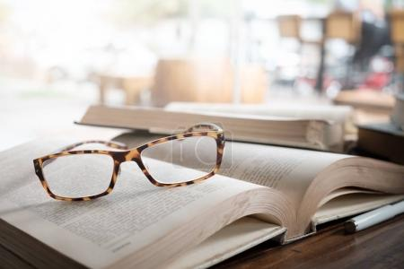 Photo pour Concept d'éducation, d'enseignement et d'apprentissage idée de fond. Lunettes sur le livre d'ouverture à la bibliothèque ou au café . - image libre de droit
