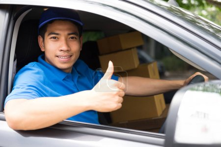 Photo for Delivery driver driving car with packages on seat outside the warehous - Royalty Free Image