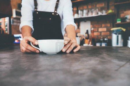 Photo pour Coupé coup de barista dans le tablier tenant une tasse de café sur le comptoir dans le café. Start up propriétaire de petite entreprise concept de nourriture et de boissons - image libre de droit