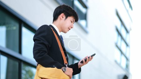 Photo for Young businessman using mobilephone app texting outside of office with skyscrapers buildings in background. Young man holding smartphone for business work. - Royalty Free Image