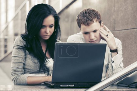 Young business couple using laptop at office building