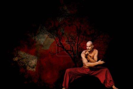 Photo pour Artiste martial qualifié en position basse avec fond rouge artistique - image libre de droit