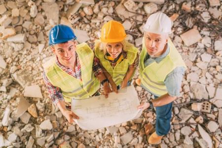Photo pour Plan d'examen de trois architectes de construction dans un bâtiment endommagé - image libre de droit