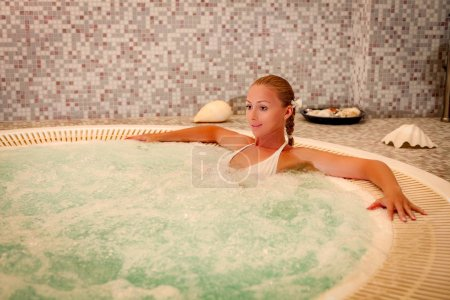 Photo for Beautiful woman enjoying and relaxing in Jacuzzi at the spa center. - Royalty Free Image