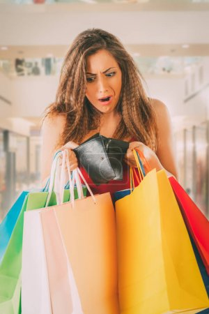 woman holding empty wallet and bags