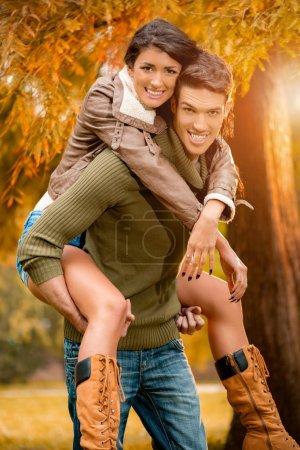 couple enjoying piggyback in forest