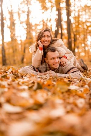 smiling couple lying on leaves in forest