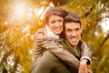 couple enjoying piggyback in forest