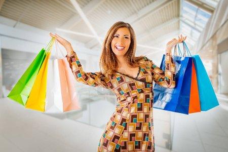 Photo pour Belle femme souriante avec des sacs à provisions multicolores dans le centre commercial, concept Shopping Time - image libre de droit