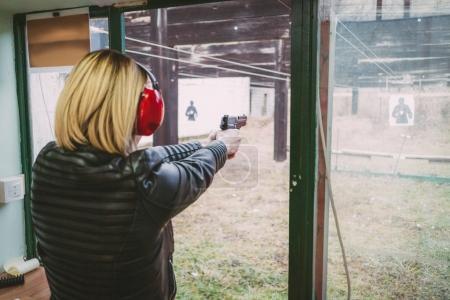 Photo pour Femme tirant avec un pistolet sur la cible au champ de tir. Vue arrière . - image libre de droit