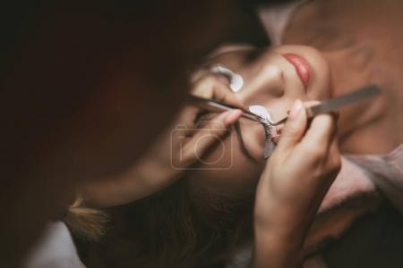 Photo pour Esthéticienne appliquant des cils allongés sur le modèle. Gros plan . - image libre de droit