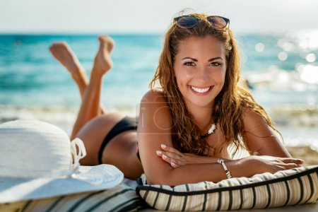 Photo for Beautiful young smiling woman enjoying on the beach. Looking at camera. - Royalty Free Image