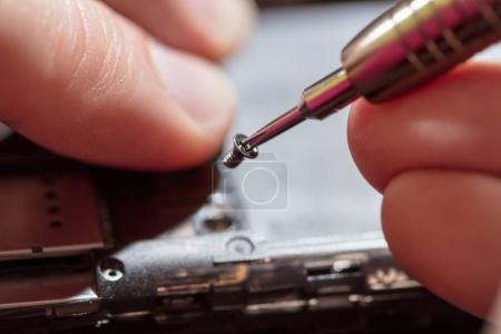 Photo pour Gros plan d'un homme de mains servising cassé smartphone. - image libre de droit