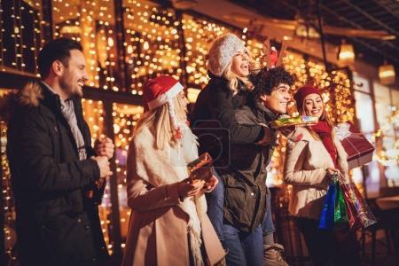 Foto de Sonriente a joven amigos celebrando la Navidad fuera y sostiene muchas compras bolsas de papel, cajas y botella de champagne en la noche de la ciudad - Imagen libre de derechos