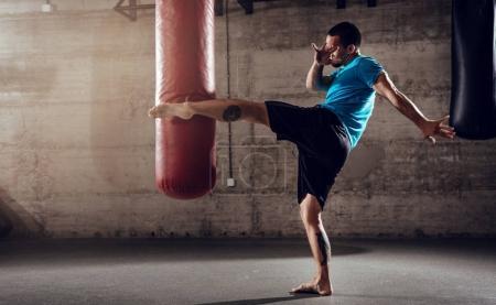 Photo pour Homme musclé poinçonnage avec sac de boxe de jambe sur Croix formation forme au gymnase. - image libre de droit