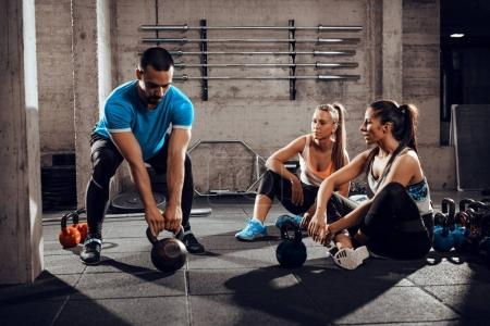 Photo for Two girlfriends exercising with a personal trainer at the gym - Royalty Free Image