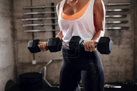 Close-up of a muscular woman doing exercise for biceps at the gym.